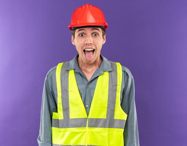 Возбужденный молодой строитель человек в униформе показывает язык