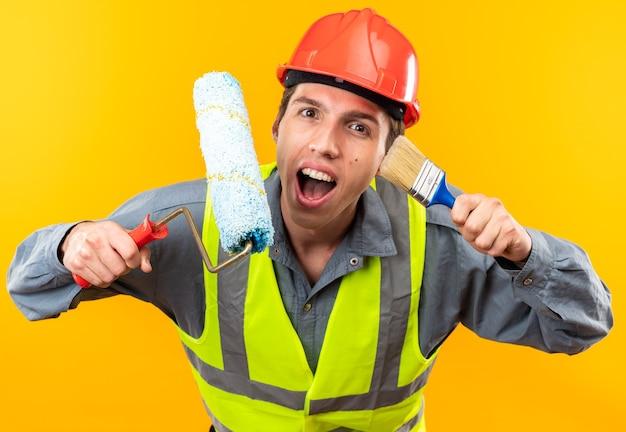 Eccitato giovane costruttore in uniforme che tiene la spazzola a rullo con pennello isolato su parete gialla