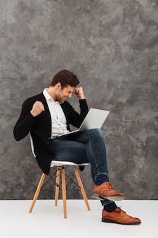 Excited молодой бизнесмен используя портативный компьютер делает жест победителя.