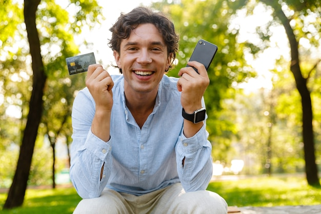 Excited young casual man holding mobile phone