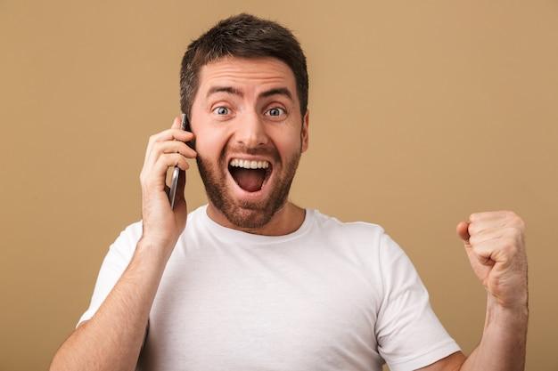 孤立した携帯電話で話している興奮した若いカジュアルな男