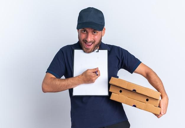 Eccitato giovane fattorino caucasico in uniforme blu e berretto con pacchi di pizza e appunti sotto il mento guardando la telecamera che punta agli appunti con penna isolata sul muro bianco