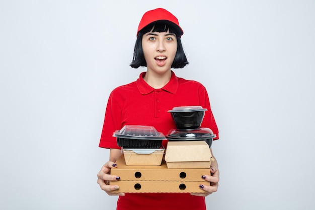 Excited young caucasian delivery woman holding food containers and pizza boxes