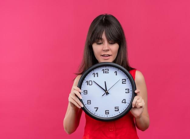 両手で時計を保持し、コピースペースで孤立したピンクの背景の時計を見て興奮した若い白人の女の子