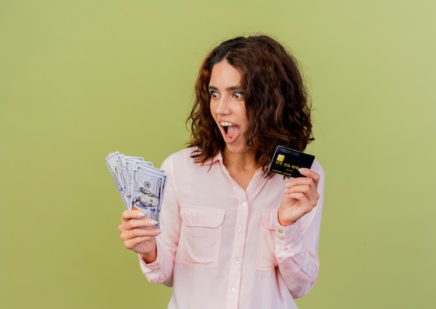 Excited young caucasian girl holds credit card and looks at money isolated on green background with copy space