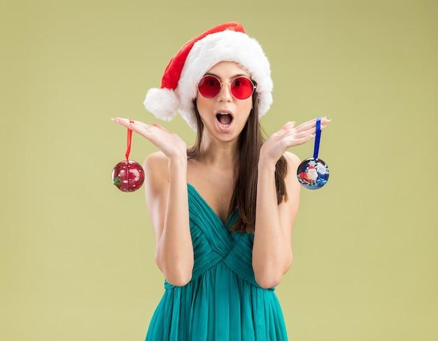 Eccitata giovane ragazza caucasica in occhiali da sole con cappello santa tenendo gli ornamenti di palla di vetro