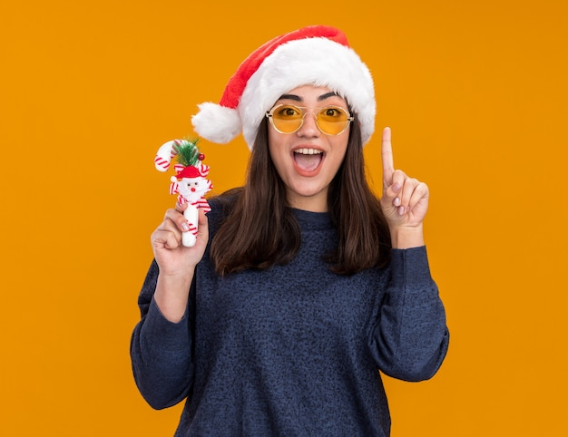 Excited young caucasian girl in sun glasses with santa hat holds candy cane and points up isolated on orange wall with copy space