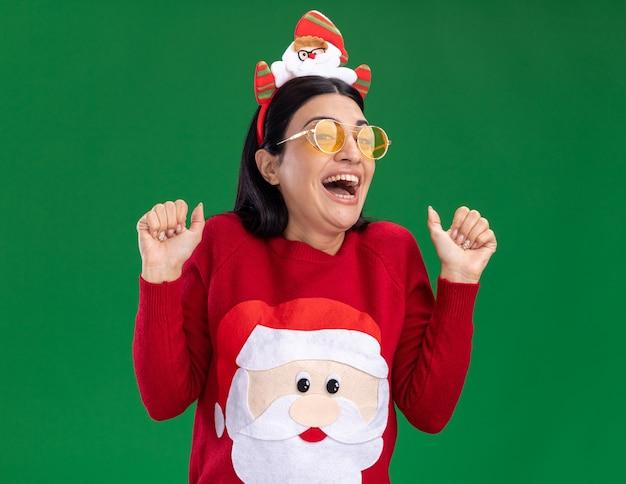 녹색 배경에 고립 엄지 손가락을 보여주는 카메라를보고 안경 산타 클로스 머리띠와 스웨터를 입고 흥분된 젊은 백인 여자