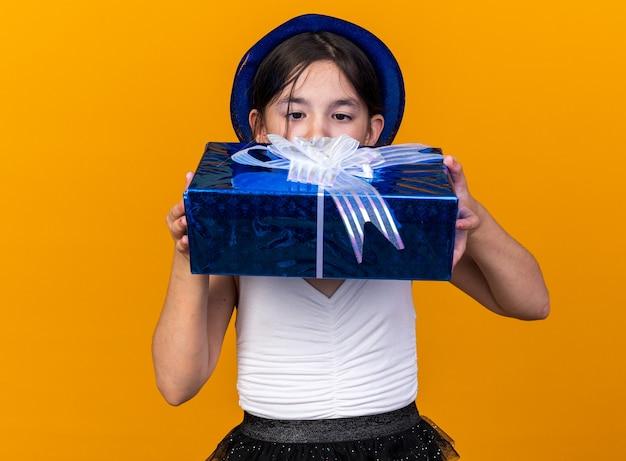 コピースペースとオレンジ色の壁に分離されたギフトボックスを保持し、見て青いパーティーハットを持つ興奮した若い白人の女の子
