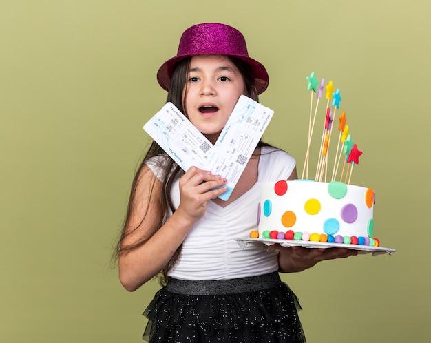 コピースペースでオリーブグリーンの壁に分離されたバースデーケーキと航空券を保持している紫色のパーティーハットを持つ興奮した若い白人の女の子