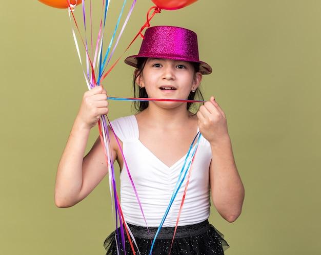 Возбужденная молодая кавказская девушка в фиолетовой шляпе держит гелиевые шары, изолированные на оливково-зеленой стене с копией пространства