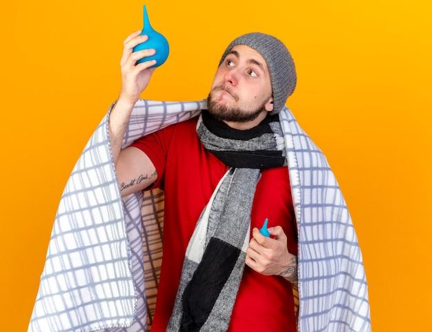 Eccitato giovane uomo malato caucasico indossando cappello invernale e sciarpa avvolta in un plaid detiene i clisteri