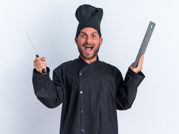 白い壁に隔離されたカメラを見て、シェフの制服とキャップ保持包丁とまな板で興奮した若い白人男性料理人