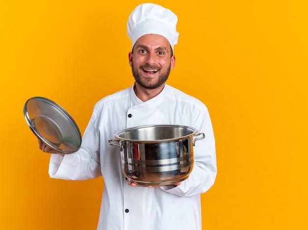 Взволнованный молодой кавказский мужчина-повар в униформе и кепке шеф-повара смотрит в камеру, держащую горшок и крышку горшка, изолированную на оранжевой стене с копией пространства