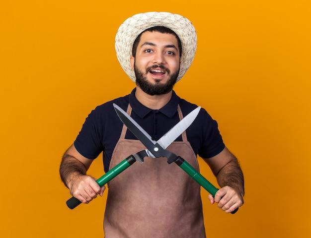 Возбужденный молодой кавказский садовник в садовой шляпе держит садовые ножницы, изолированные на оранжевой стене с копией пространства