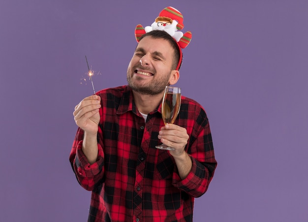 休日の線香花火と紫色の背景に分離された目を閉じて笑っているシャンパンのガラスを保持しているサンタクロースのヘッドバンドを身に着けている興奮した若い白人男性