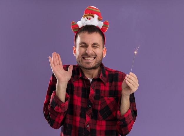 Возбужденный молодой кавказский мужчина в головной повязке санта-клауса держит праздничный бенгальский огонь, показывая пустую руку, улыбаясь с закрытыми глазами, изолированными на фиолетовом фоне