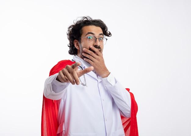 赤いマントと聴診器を首にかけた医者の制服を着た光学ガラスの興奮した若い白人のスーパーヒーローの男は、口に手を置き、白い壁に隔離されたポイント