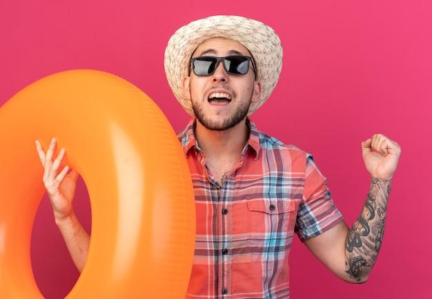 Eccitato giovane viaggiatore caucasico con cappello da spiaggia di paglia in occhiali da sole che tiene anello da bagno e tiene il pugno alzando lo sguardo isolato sulla parete rosa con spazio di copia