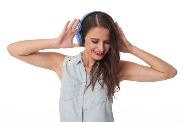 青いワイヤレスヘッドフォンで音楽を聴いているノースリーブのシャツを着た興奮した若い白人女性