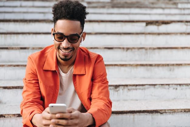 Eccitato giovane affascinante uomo barbuto in occhiali da sole e giacca arancione sorride sinceramente, si siede sulle scale e tiene il telefono fuori