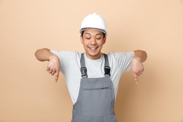 안전 헬멧과 유니폼을 입고 아래를 가리키는 흥분된 젊은 건설 노동자