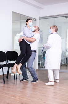 Excited young couple after receiving good from doctor with face mask in hospital waiting area