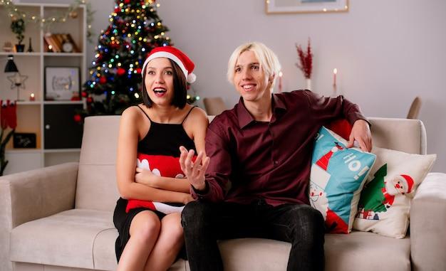 Возбужденная молодая пара дома на рождество в шляпе санта-клауса сидит на диване в гостиной и смотрит телевизор, девушка держит рождественскую подушку, парень держит руку в воздухе