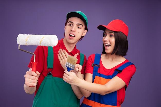 Eccitato giovane coppia in uniforme da operaio edile e berretto che tiene e punta al rullo di vernice ragazza che allunga il pennello guardando il rullo di vernice isolato sul muro viola