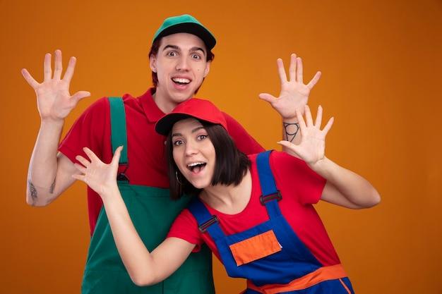 Eccitato giovane coppia in uniforme da operaio edile e berretto guardando la telecamera che mostra le mani vuote isolate sulla parete arancione