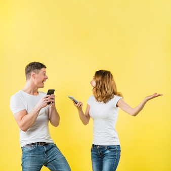 Excited young couple holding mobile phone in hand shouting with joy