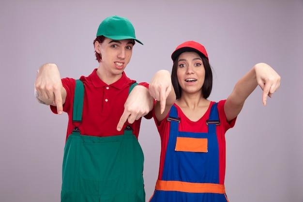 건설 노동자 유니폼과 모자를 아래로 가리키는 흥분된 젊은 부부