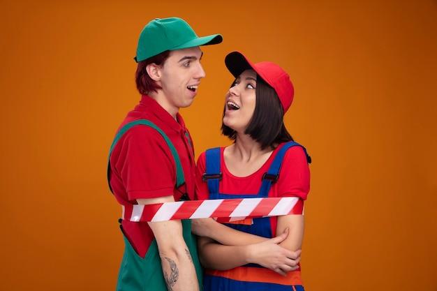 건설 노동자 유니폼을 입고 모자를 쓰고 안전 테이프로 묶인 흥분한 젊은 부부는 복사 공간이 있는 주황색 벽에 격리된 팔에 손을 얹고 있는 소녀를 바라보고 있습니다.