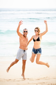 Excited young couple jumping together on beach