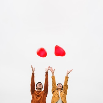 Excited young couple letting go balloons