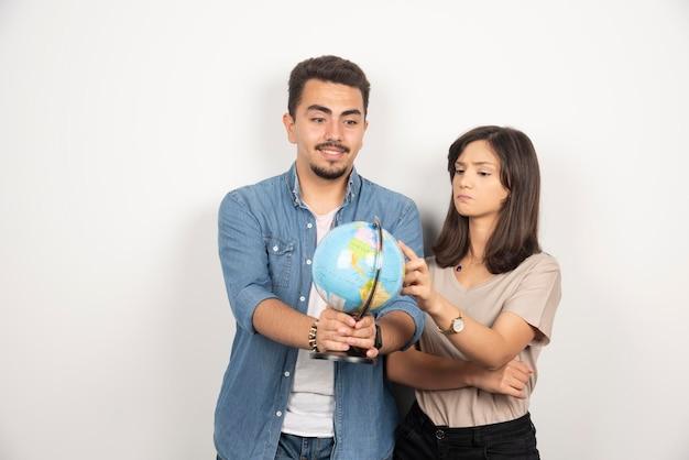 Giovani coppie emozionanti che osservano sul globo della terra.