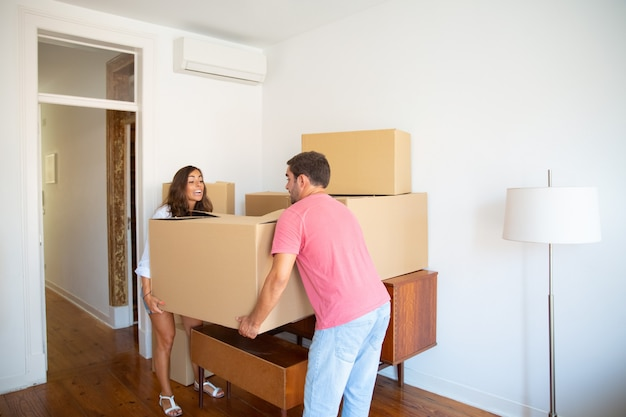 カートンボックスを慎重に運んで、新しいアパートに移動する興奮した若いカップル