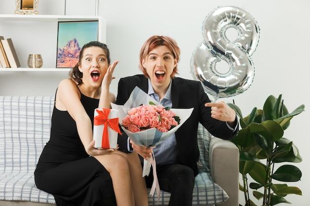 リビングルームのソファに座っている花束とプレゼントを保持している幸せな女性の日に興奮した若いカップル