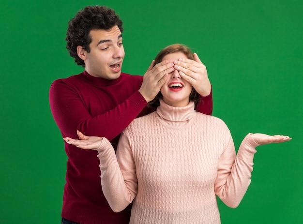 발렌타인 데이에 흥분한 젊은 부부 남자는 손으로 눈을 가리고 녹색 벽에 고립 된 빈 손을 보여주는 그녀를보고 여자 뒤에 서있는 남자