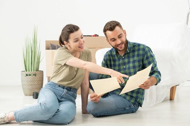 床に座って、家の計画を使用して新しいアパートのインテリアデザインについて話し合う興奮した若いカップル