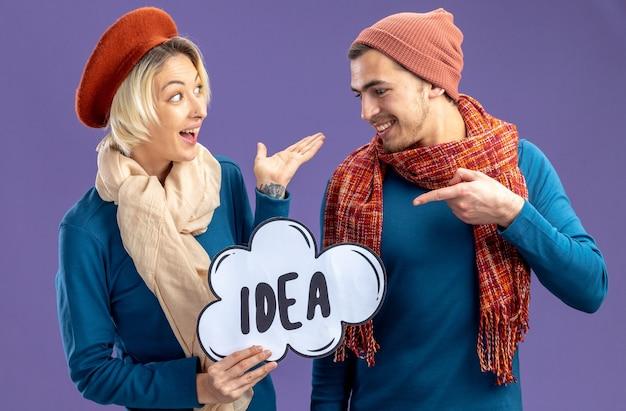 バレンタインデーの開催にスカーフと帽子をかぶって、青い背景で隔離のアイデアバブルを指す興奮した若いカップル