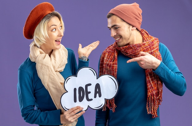 Excited young couple wearing hat with scarf on valentine's day holding and points at idea bubble isolated on blue background