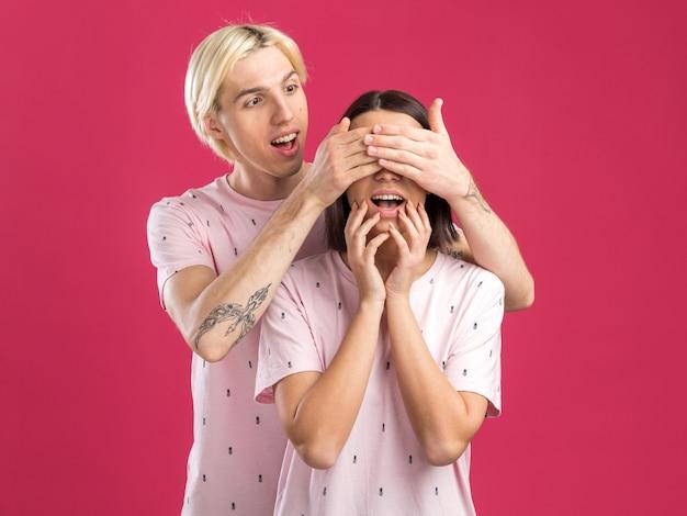 분홍색 벽에 격리된 손으로 턱을 만지는 여성을 바라보며 손으로 눈을 가리고 있는 여성 뒤에 서 있는 잠옷을 입은 흥분한 젊은 부부