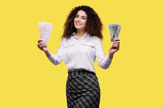 복권으로 돈을 들고 노란색 배경 위에 절연 성공을 축하하는 흥분된 젊은 곱슬 소녀