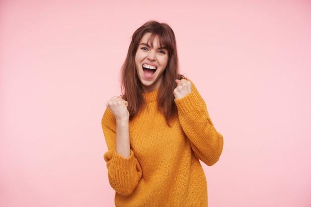 Возбужденная молодая темноволосая женщина держит рот открытым, глядя, держа поднятые руки, стоя над розовой стеной в повседневной одежде