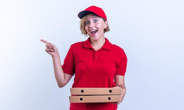 Eccitato giovane ragazza delle consegne che indossa l'uniforme e il cappuccio che tiene scatole per pizza e punti sul lato isolato sul muro bianco con spazio di copia