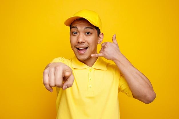 모자와 유니폼을 입고 전화 제스처를하고 카메라를 가리키는 흥분된 젊은 배달 남자