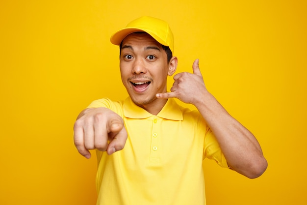 Excited young delivery man wearing cap and uniform looking and pointing at camera doing call gesture