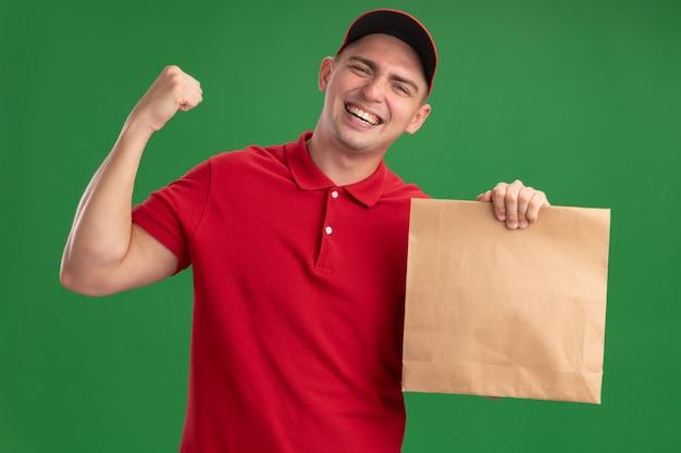Eccitato giovane fattorino che indossa l'uniforme e cappuccio che tiene il pacchetto di cibo di carta che mostra sì gesto isolato sulla parete verde
