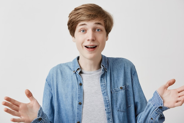 Excited young fair-haired guy in denim clothes happy that friends came on party, raises hands with enjoyment, glad to recieve congratulations and presents, celebrates his enrollment to university